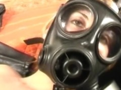 Blonde in gas mask on bed