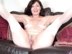 Charming auntie Kitty is about to take off her panties and masturbate on the couch
