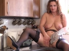 Hot milf with ample assets is wearing stockings and garter belt in the kitchen and masturbating