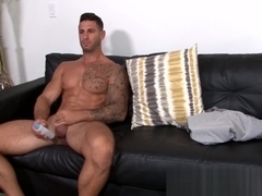 Inked military hunk wanks rock solid cock on sofa solo